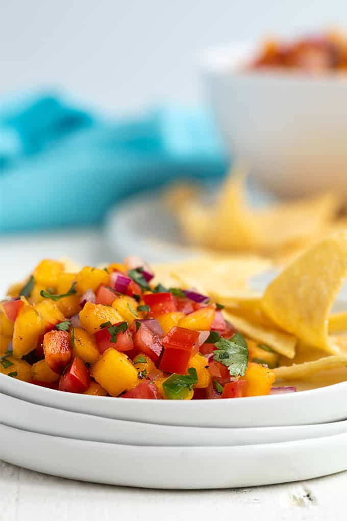 Peach salsa and tortilla chips on a white appetizer plate