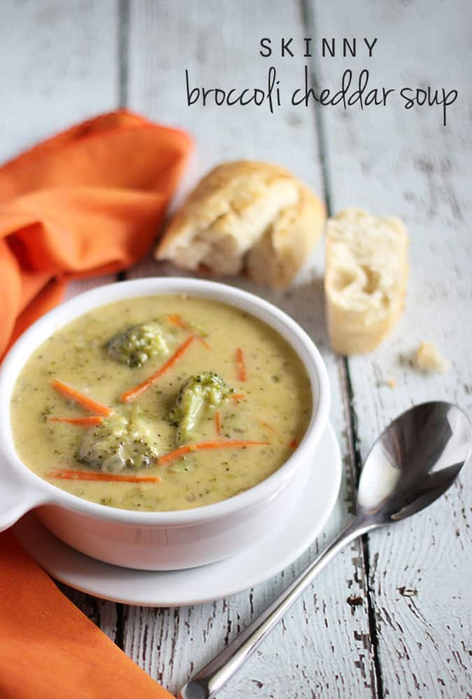 Broccoli cheese soup in a white bowl by an orange napkin and French bread.