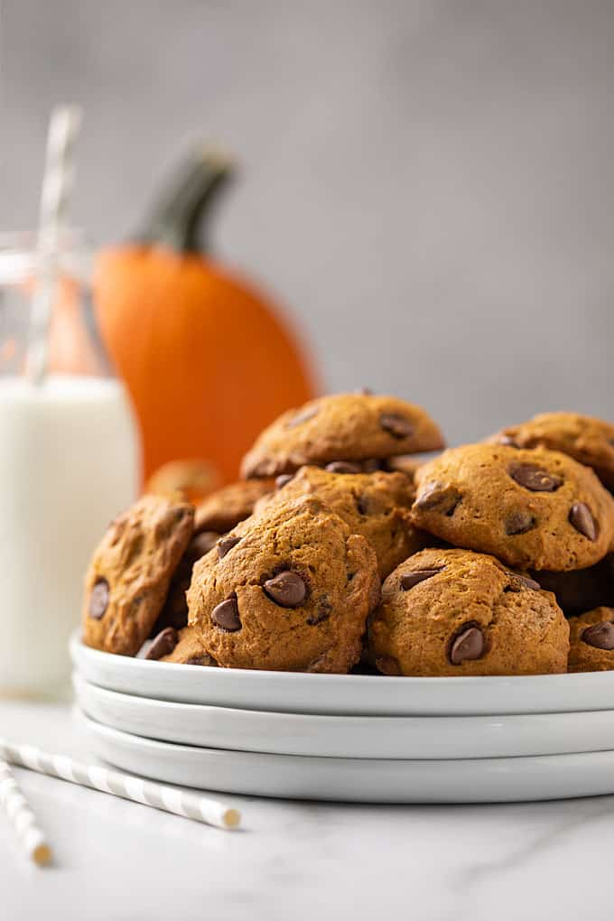 Cookies on a white plate with a glass of milk and a pumpkin in the background