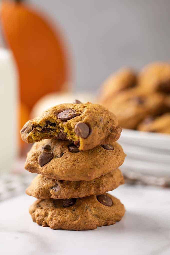 Closeup view of a stack of 4 pumpkin chocolate chip cookies.  Top cookie has been bitten.