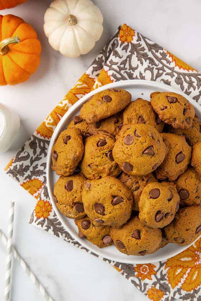 Overhead view of pumpkin chocolate chip cookies on a round white plate
