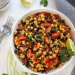 Southwestern Succotash in a round white bowl beside a grey napkin.