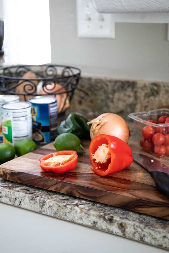 Red bell pepper, yellow onion, lime and poblano pepper on a wooden cutting board.