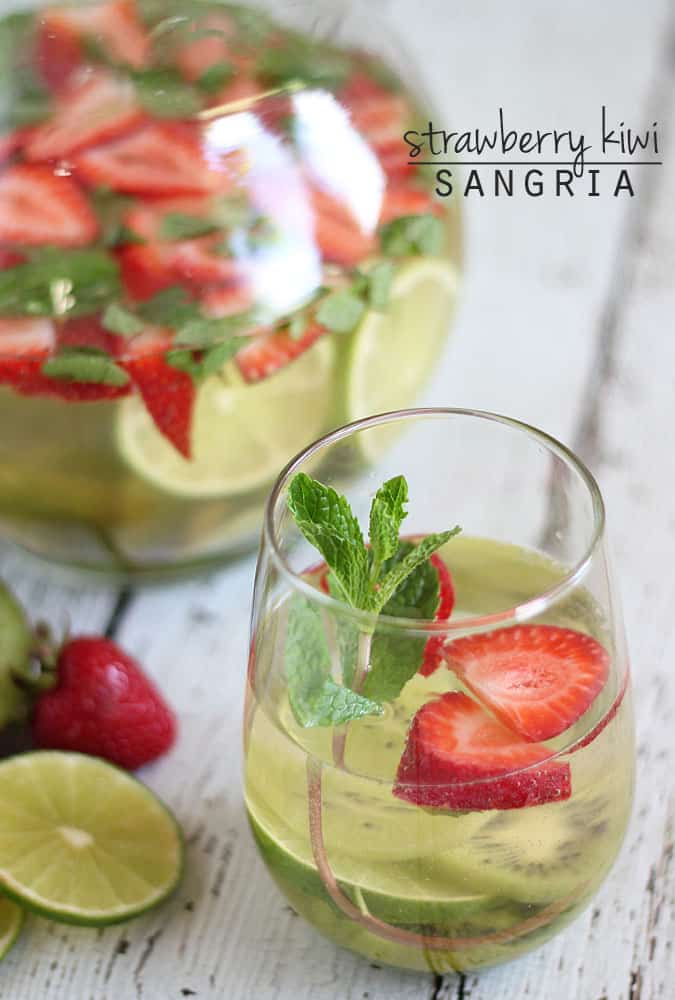 Strawberry Kiwi Sangria in a glass in front of a glass pitcher