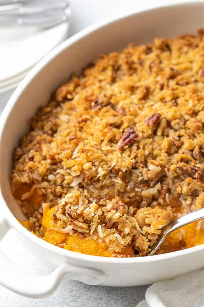 Sweet potato souffle in a white oval baking dish with a serving spoon