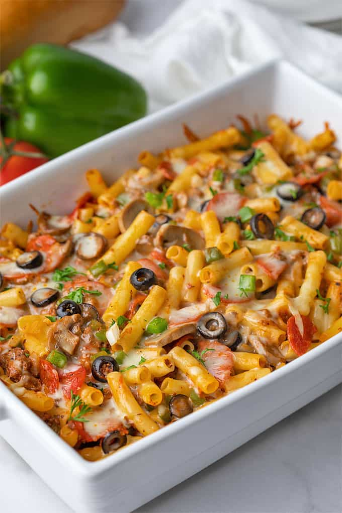 Pizza casserole with pepperoni, pasta and vegetables in a white baking dish