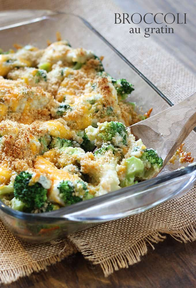 Baked broccoli with cheese and bread crumbs in a glass baking dish with a wooden spoon.