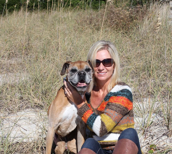 A woman with blonde hair hugging a fawn boxer dog on the beach.
