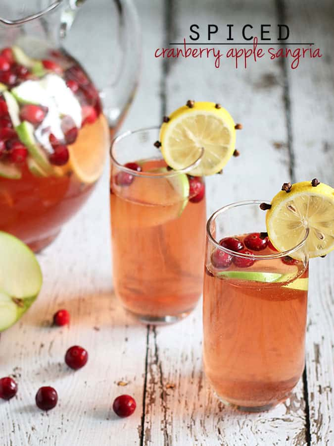 Two glasses of sangria garnished with a clove-studded lemon wheel.