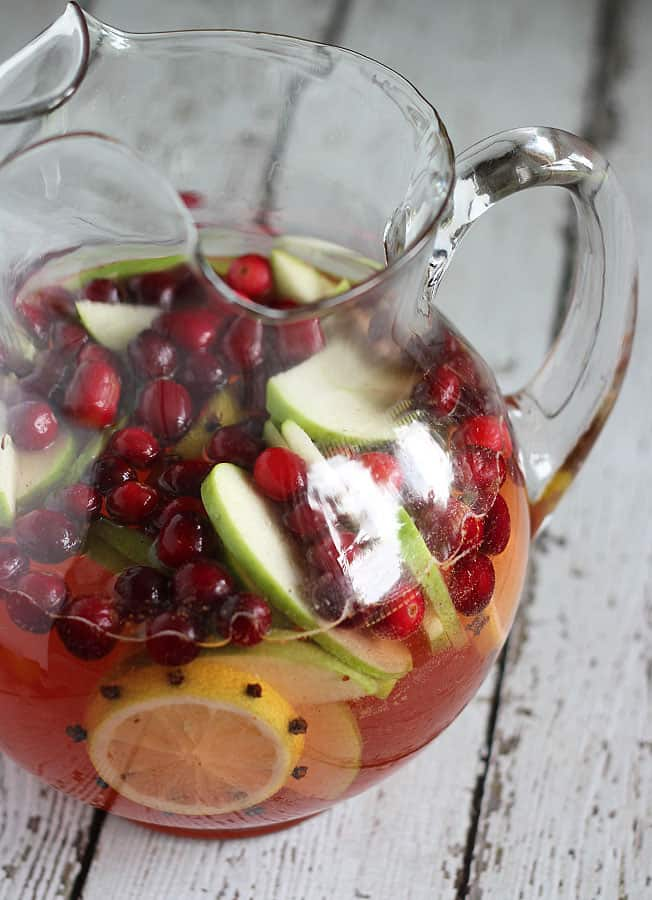 Front view of sangria in a pitcher on a white wood surface.