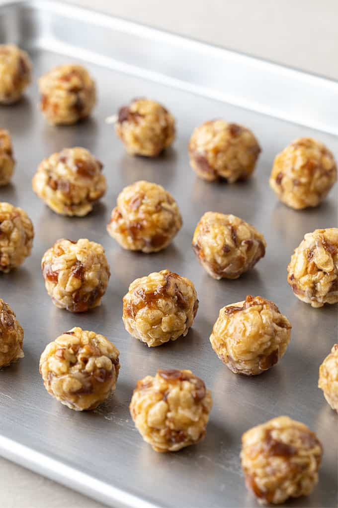 Date balls with coconut on a baking sheet.