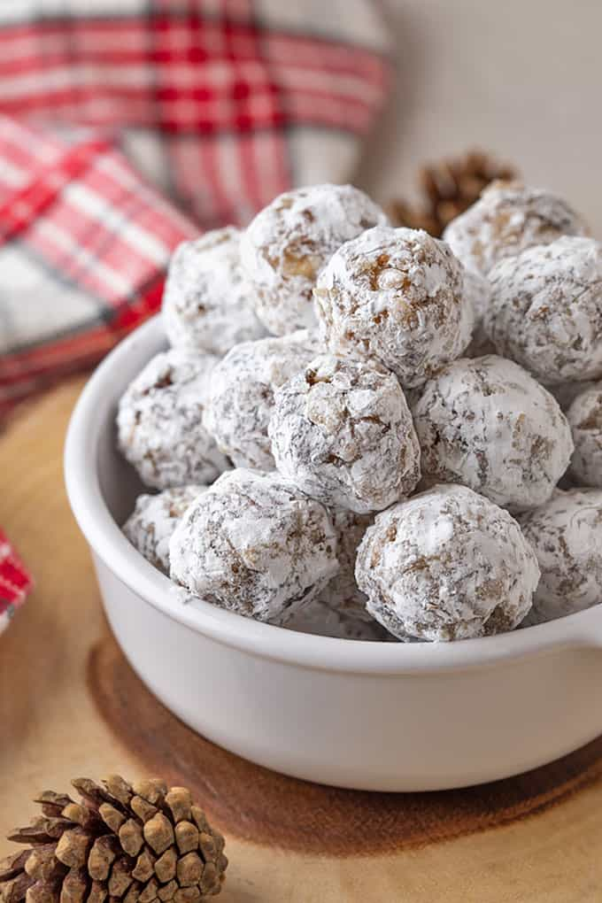 Bourbon Coconut Date Balls in a white bowl.  A checked towel is in the background.