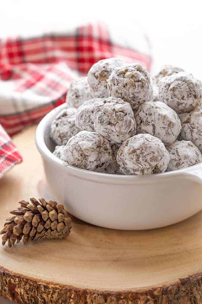 Date balls in a white bowl on a wooden trivet.