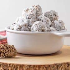 Date balls in a white bowl on a wooden trivet