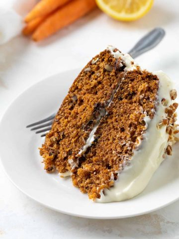 A slice of carrot cake on a white plate with a fork.