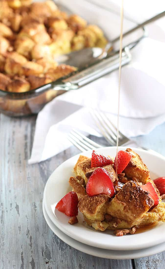 Syrup being drizzled on French toast casserole topped with sliced strawberries on a white plate.