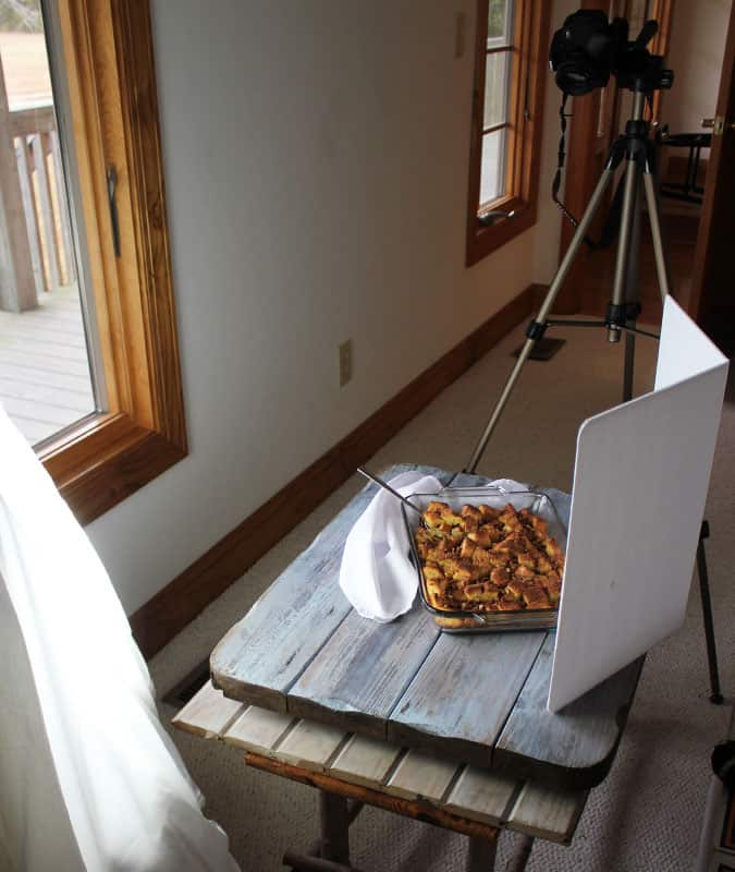 Behind the scenes view of photographing a casserole by a window.