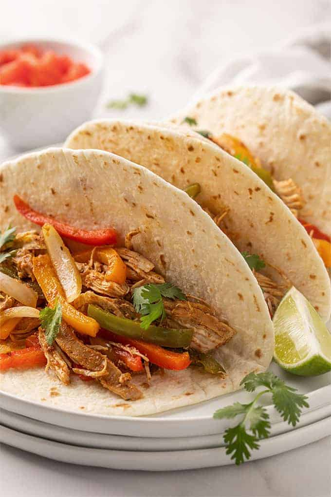 Three chicken fajitas on a white plate beside a lime wedge