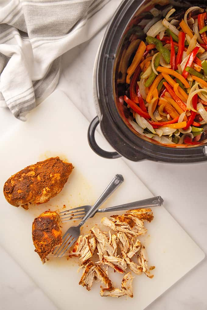 Slow cooked chicken being shredded with 2 forks beside a crock pot with peppers and onions