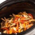 Chicken fajita mixture in an oval slow cooker.