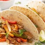 A closeup of three chicken fajitas on a white plate beside a lime wedge.
