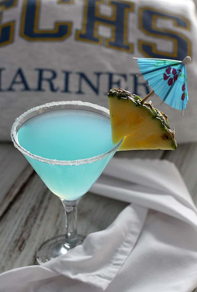 A blue martini with a sugar rim garnished with pineapple and a cocktail umbrella.