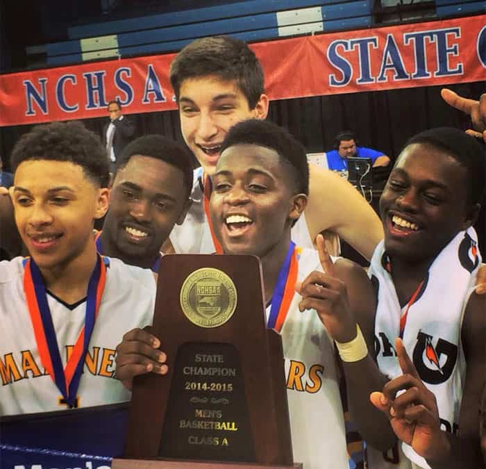 Five young male basketball players in uniform smiling and holding a state championship plaque.