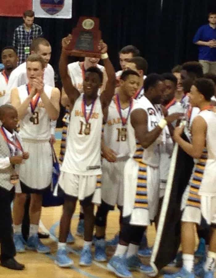 Several young male basketball players in uniform on a basketball court smiling. One is holding a plaque in the air.