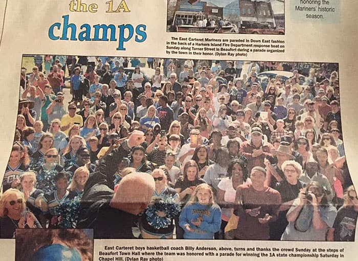 A newspaper announcing state basketball champions with a photo of several people celebrating.