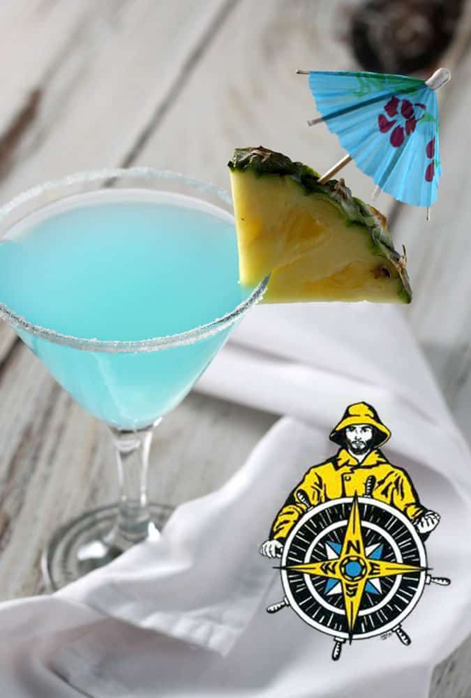 A blue martini garnished with pineapple and an umbrella. A mariner logo is at bottom right of image.