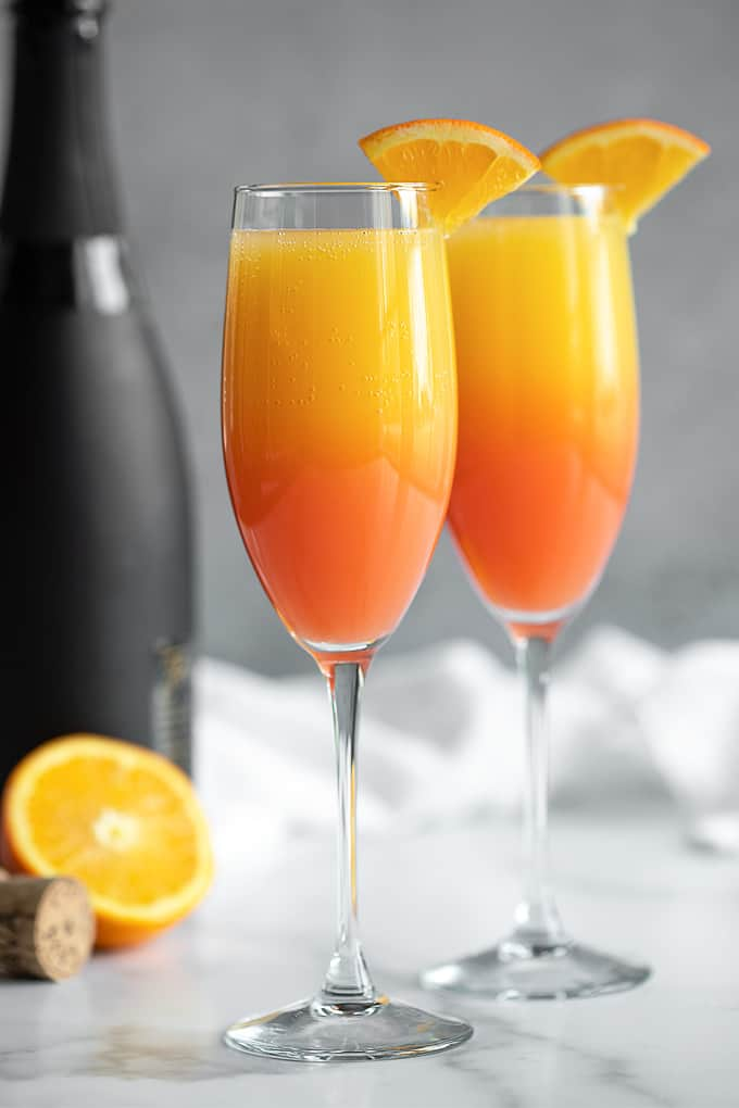 Two mimosas garnished with orange slices. A black bottle of champagne and an orange is in the background.
