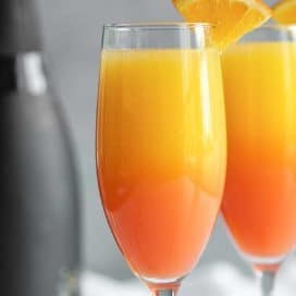 Two mimosas with a black bottle of champagne in the background.