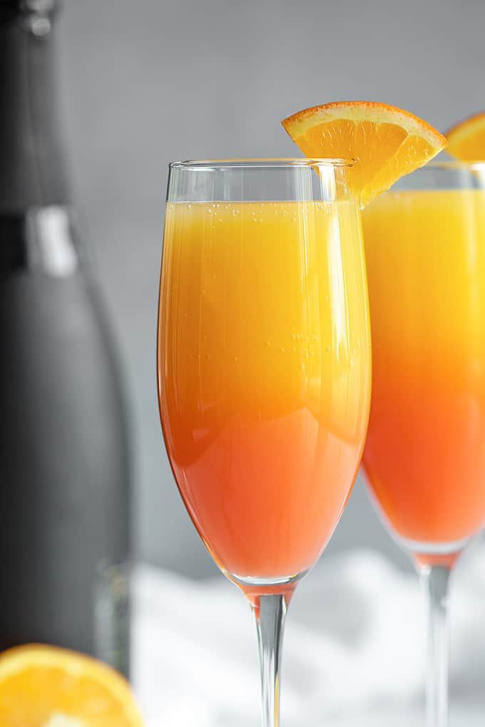 A closeup of two mimosas in champagne glasses.