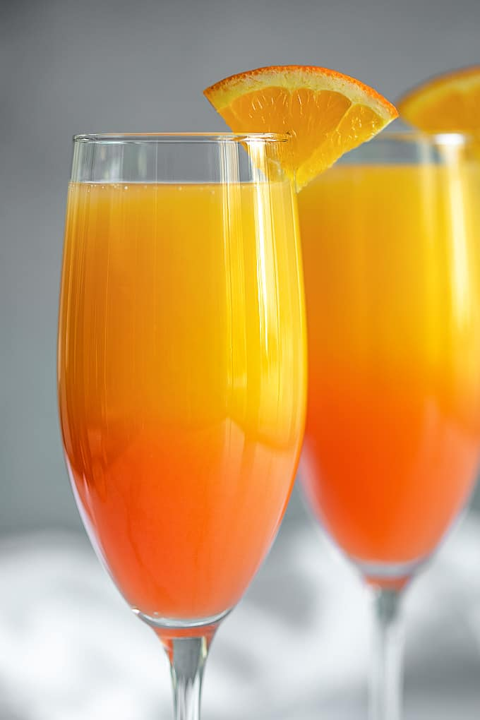 A closeup of two mimosas garnished with orange slices.