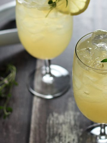Two whiskey and lemonade cocktails. A sprig of thyme, a lemon and lemon squeezer are in the background.