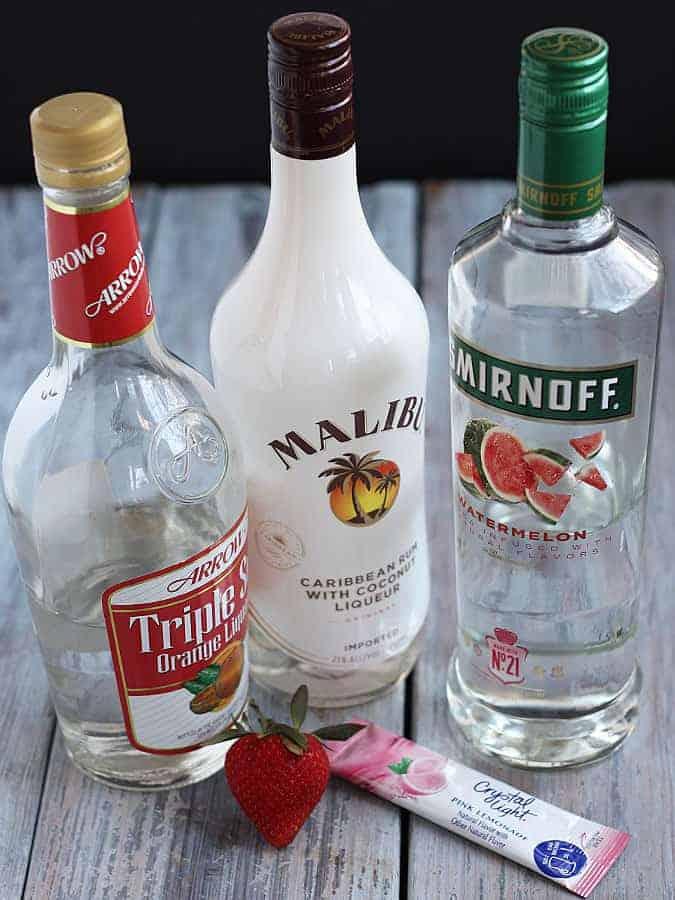Bottles of orange liqueur, rum, vodka and a packet of pink lemonade powdered drink mix.