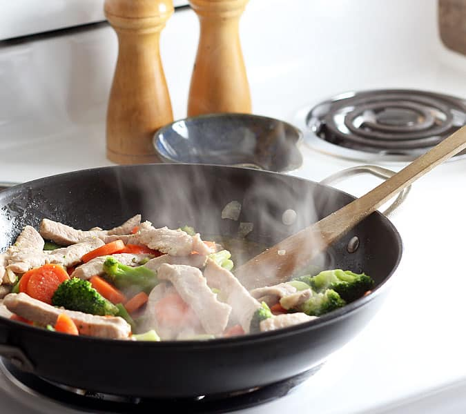 Pork strips and vegetables cooking in a skillet on a white stove.