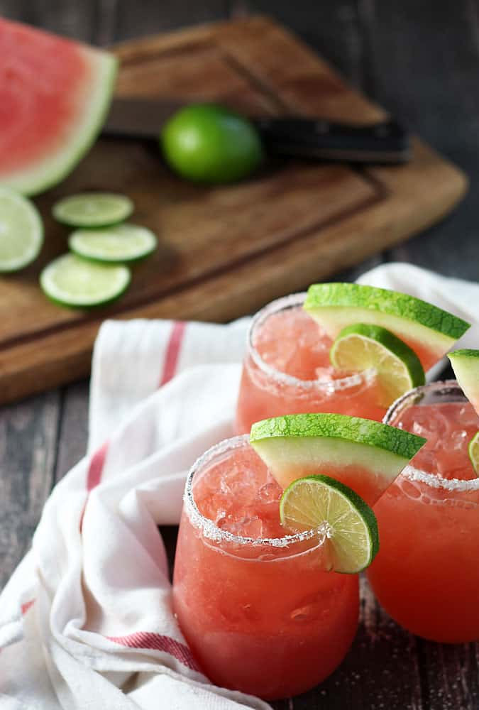 Three glasses of watermelon margaritas rimmed with salt. A cutting board is in the background.