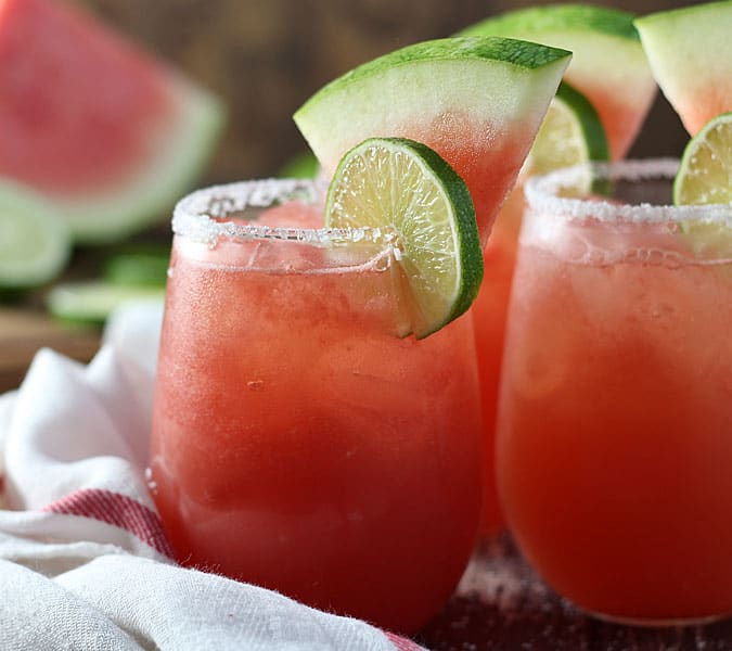 Closeup front view of margaritas garnished with lime and fresh watermelon slices.