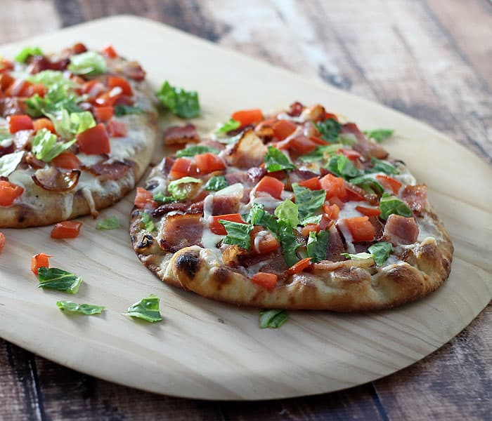 Two flatbread pizzas on a wooden pizza peel.
