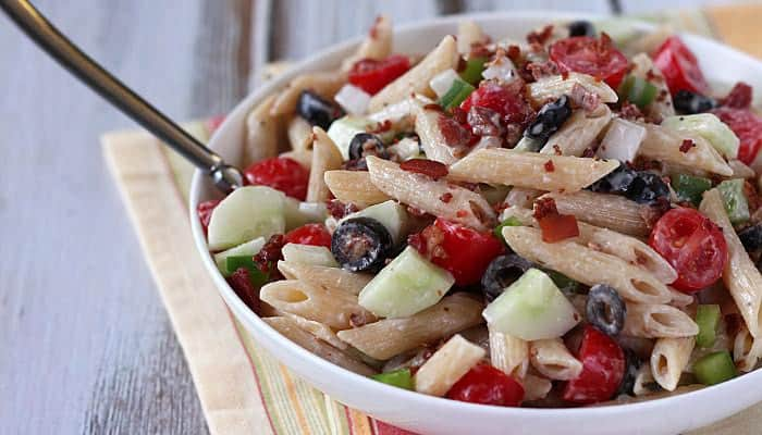 Pasta salad in a white bowl with a serving spoon on a folded striped napkin.