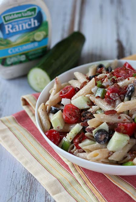 Pasta salad in a white bowl over a striped napkin.  A bottle of salad dressing and a cucumber is in the background.