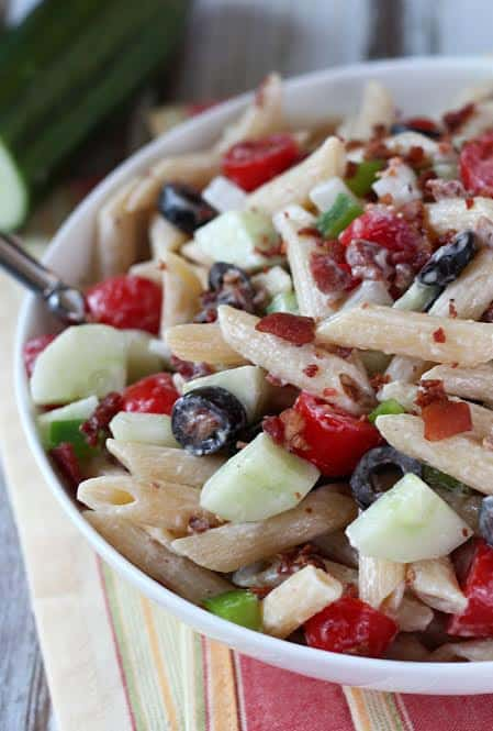 Closeup of penne pasta with vegetables, bacon, olives, and dressing in a white bowl with a serving spoon.
