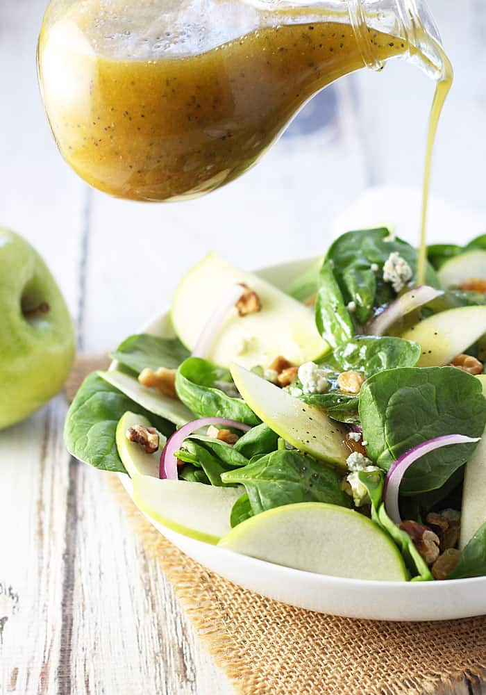Pouring poppy seed dressing on a salad with spinach and apples in a white bowl.
