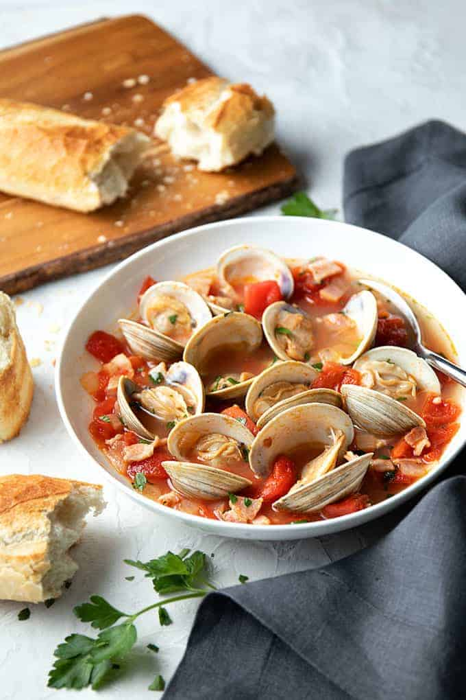 Steamed clams with smoky bacon and tomatoes in a white bowl with a spoon and French bread on a wooden cutting board.