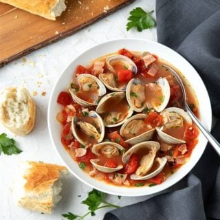 Steamed clams with smoky bacon and tomatoes in a white bowl and French bread on a wooden cutting board.