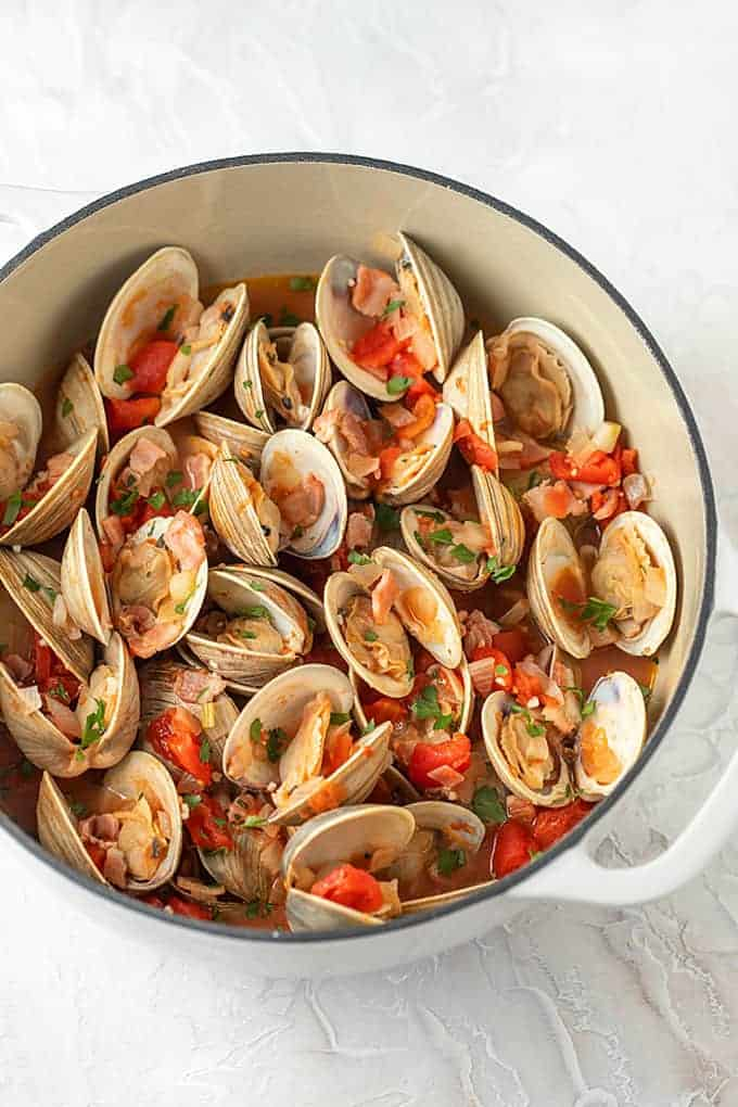 Steamed clams with bacon and tomatoes in a white dutch oven.