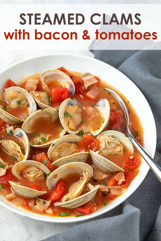 Steamed clams with smoky bacon and tomatoes in a white bowl with a spoon.