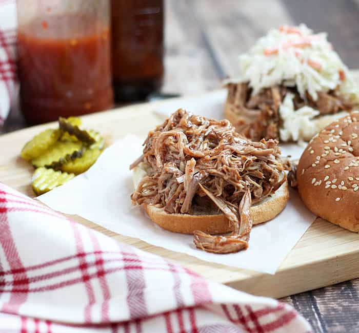 Pulled pork on a bun on a piece of parchment paper. A bottle of sauce is in the background.