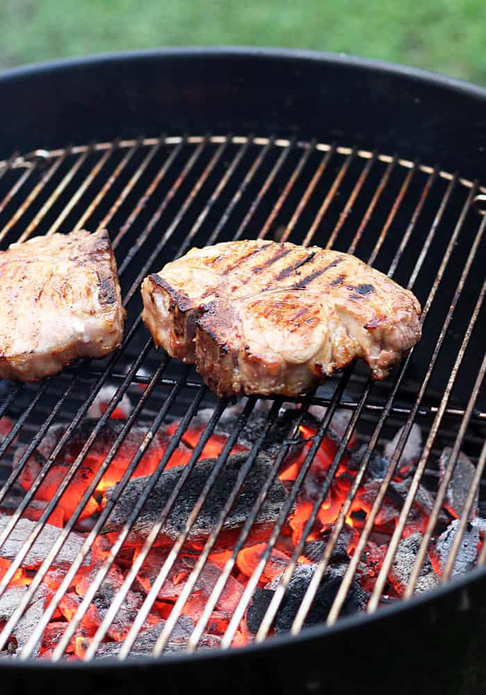Two pork chops being grilled on a grate over hot coals.